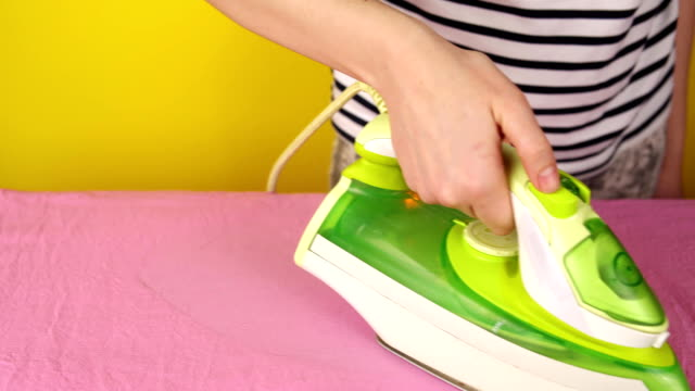Girl irons bed linen on an ironing board, household chores. video