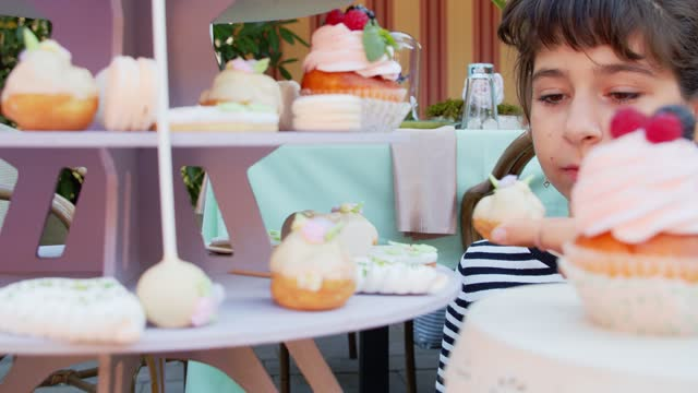 Girl is choosing delicious cupcakes on a buffet at a children's party, 4k