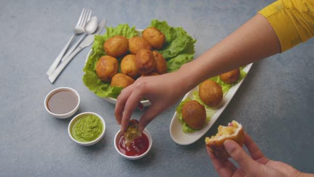 vídeos de stock, filmes e b-roll de uma garota está comendo pães fritos com molhos e chutney - comida salgada