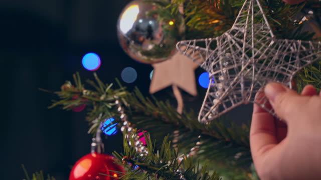 a girl is hanging christmas decoration on christmas tree with sparkling led. - jodła filmów i materiałów b-roll