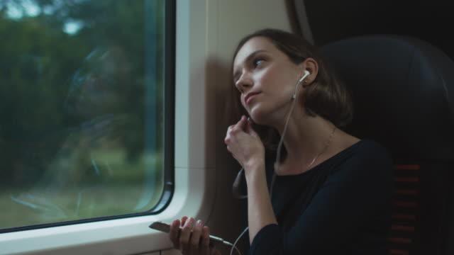 vidéos et rushes de la fille écoute une musique pendant le voyage en train - casque audio