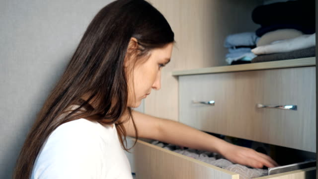 girl is looking for something among her things in a drawer in the closet the girl is looking for something among her things in a drawer in the closet. cabinet stock videos & royalty-free footage