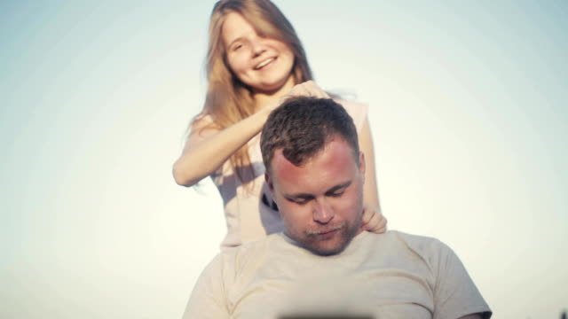 Girl is massaging the head of the guy