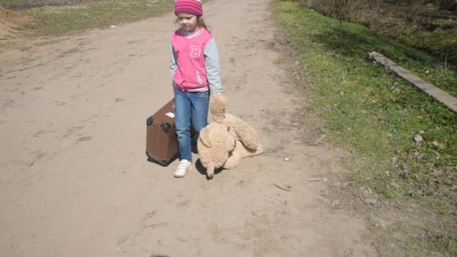 girl is on the road with a suitcase and a toy bear in his hand - сбежавший из дома стоковые видео и кадры b-roll