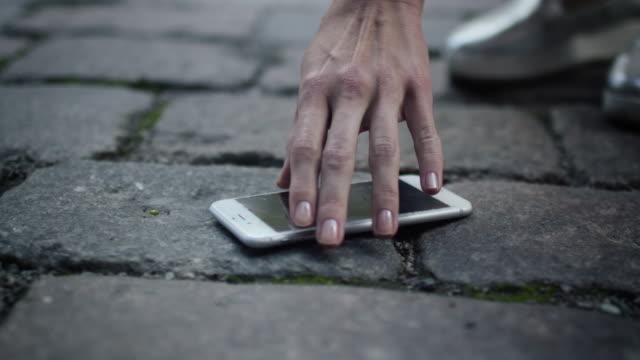 女の子は路上で壊れた携帯電話を拾っています。 - 持ち上げる点の映像素材/bロール