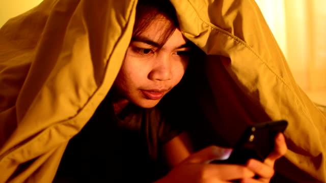girl is playing game on the phone under the covers. - kołdra filmów i materiałów b-roll