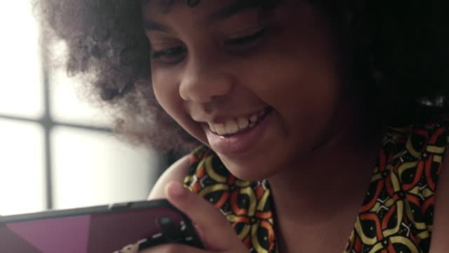 girl is playing on the smartphone - развлекательные игры стоковые видео и кадры b-roll