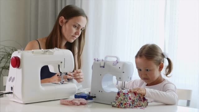 a girl is sewing on a machine. mom shows how to work with equipment. close-up. - sarta video stock e b–roll