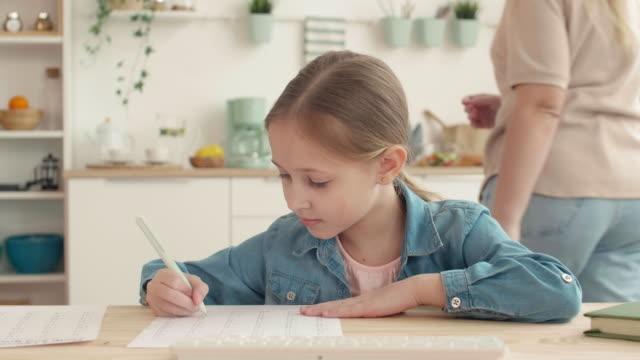 девушка учится онлайн на кухне - covid testing стоковые видео и кадры b-roll