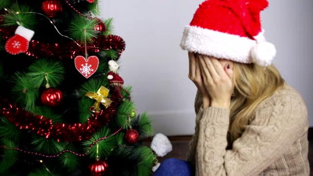女の子は驚いて、彼女の新年の贈り物を喜ぶ - サンタの帽子点の映像素材/bロール