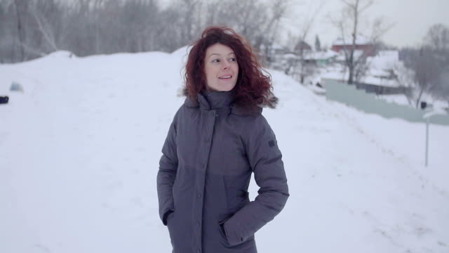A girl is walking on a snow-covered park. video