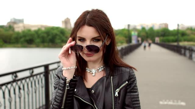 Jeune fille marche sur le pont et met des lunettes de soleil. - Vidéo