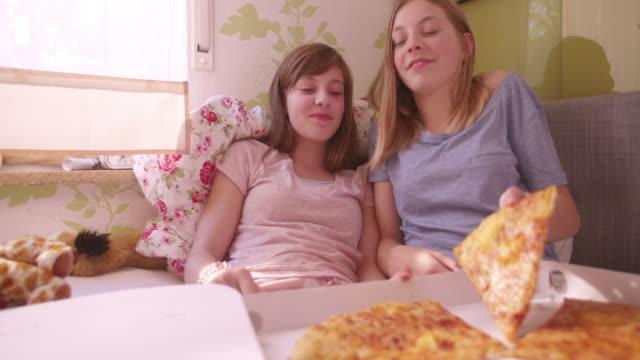 mädchen spaß und füttern ihrem freund großes stück pizza - teenage friends sharing food stock-videos und b-roll-filmmaterial