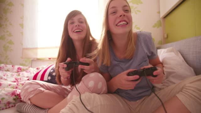 開玩笑地在玩電腦遊戲的同時推她的朋友的女孩 - 休閒器具 個影片檔及 b 捲影像