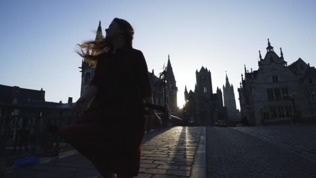 vídeos de stock, filmes e b-roll de garota dançando alegremente no centro da cidade de ghent - castelo