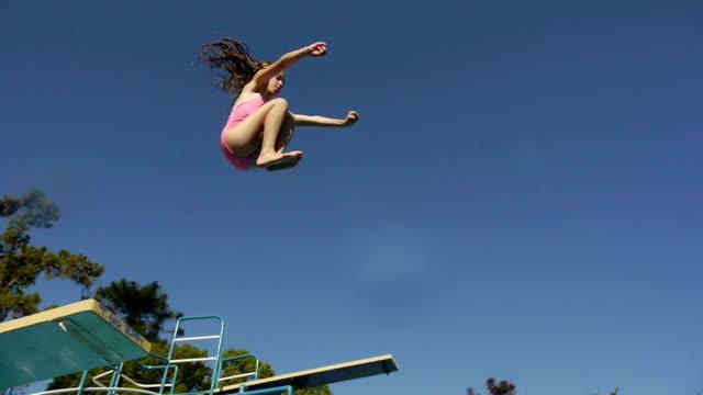 vídeos de stock e filmes b-roll de menina saltar de trampolim e mergulho na piscina. - jump pool, swimmer