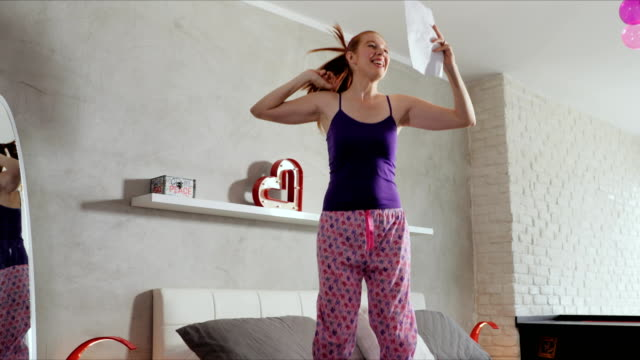 girl jumping on bed success for happy young woman - esame università video stock e b–roll