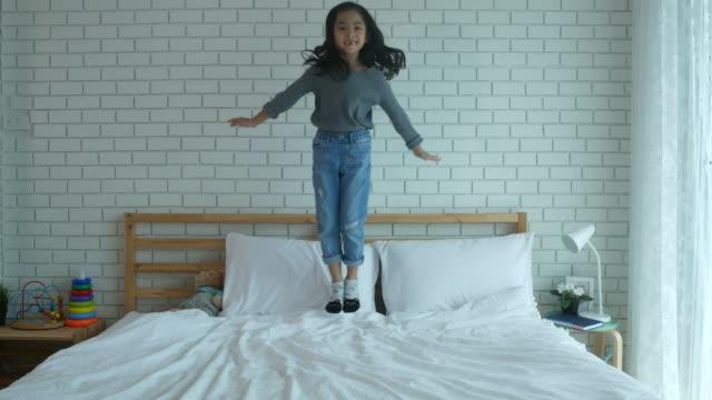 vídeos y material grabado en eventos de stock de niña saltando sobre la cama - colchón