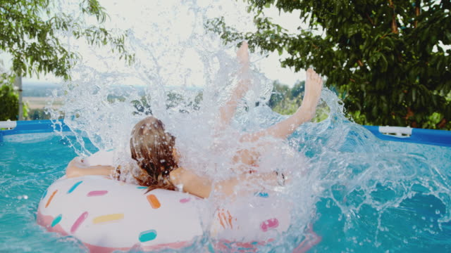 stockvideo's en b-roll-footage met ms girl springen op opblaasbare ring in zwembad - opblaasband