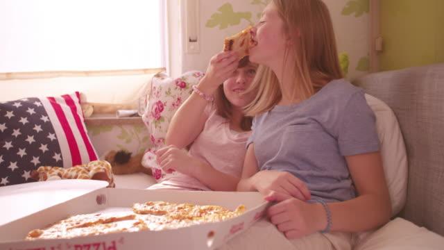 mädchen lachen und füttern ihrem freund pizza im bett - teenage friends sharing food stock-videos und b-roll-filmmaterial