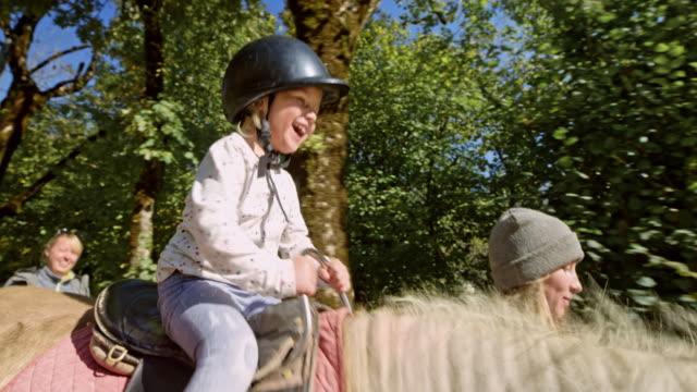 girl laughing while riding on a horse in sunshine - attività equestre ricreativa video stock e b–roll