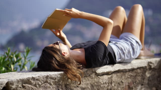 girl laying on her back on stone wall reading a book - mountain top filmów i materiałów b-roll