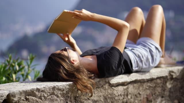 책을 읽고 하는 돌 벽에 그녀를 다시에 누워 소녀 - mountain top 스톡 비디오 및 b-롤 화면