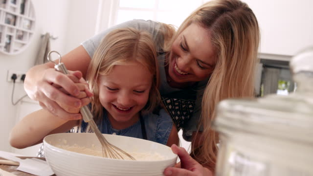 Girl learning baking with her mother. Cute little girl with her mother mixing batter in a bowl. Mother and daughter baking in kitchen. recreational pursuit stock videos & royalty-free footage