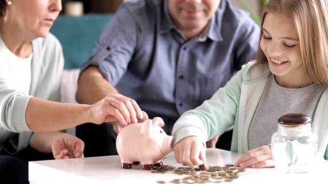 mädchen lernen, geld zu sparen - sparsamer lebensstil stock-videos und b-roll-filmmaterial
