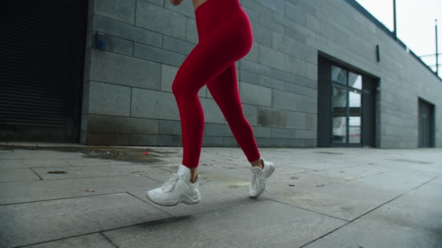 Girl legs running outdoor in slow motion. Close up female legs running on street
