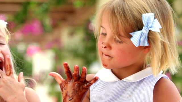 girl licking melted chocolate from fingers - slicka bildbanksvideor och videomaterial från bakom kulisserna