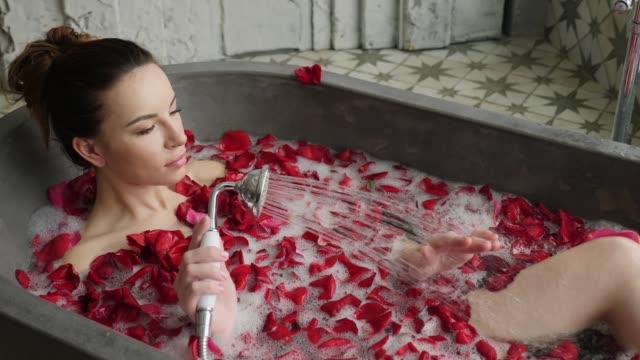 fille se trouve dans un bain de pierre avec de la mousse et des pétales se lave - Vidéo