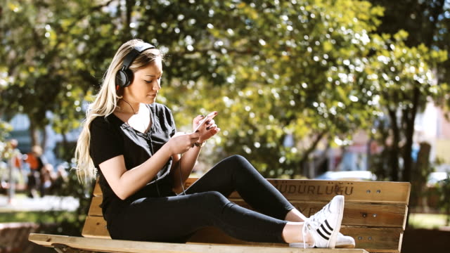 Girl listenin music with phone in public park video