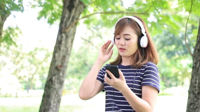 Girl listening and enjoying the music with smartphone in garden, She is happiness on casual day
