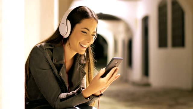 Girl listening to music from smart phone in the night