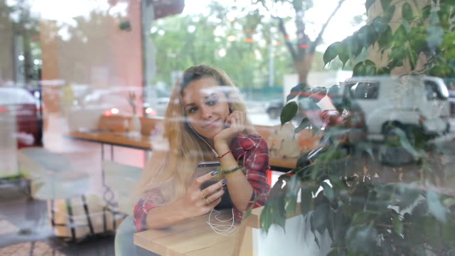 vídeos de stock e filmes b-roll de girl listening to music in modern cafe . street traffic is on window reflection - bar local de entretenimento