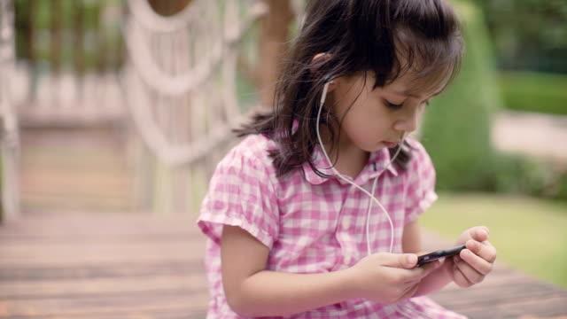 bir kız parkta müzik dinlemek ve mutlu hissediyorum - kulak i̇çi kulaklık stok videoları ve detay görüntü çekimi