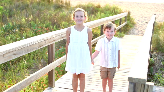 Girl, little brother at beach running on wooden walkway video