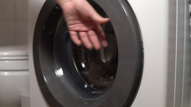 Girl loads dirty things into the washing machine close-up