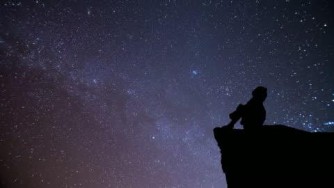 ragazza guarda al cielo notturno con la meteora - guardare in una direzione video stock e b–roll