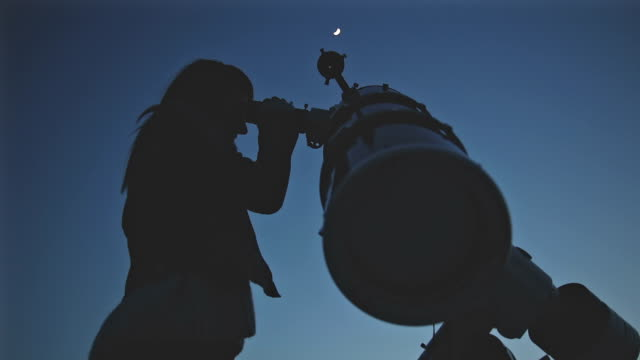 girl looking at the moon through a telescope. - astronomia video stock e b–roll
