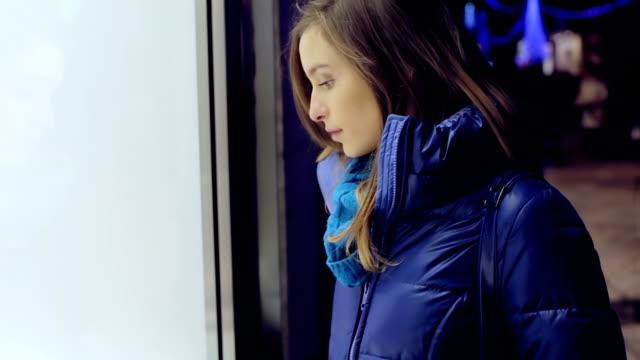 stockvideo's en b-roll-footage met meisje kijkend naar de etalage alvorens de winkel - raam bezoek