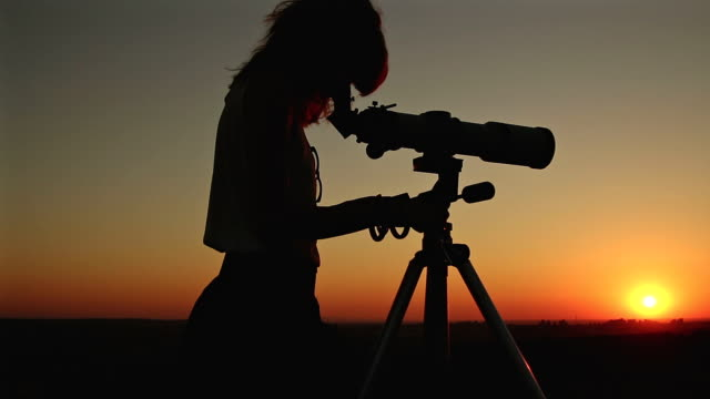 Girl looking at the stars through a telescope. video