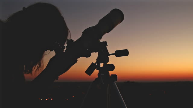 Girl looking at the stars with telescope beside her. video