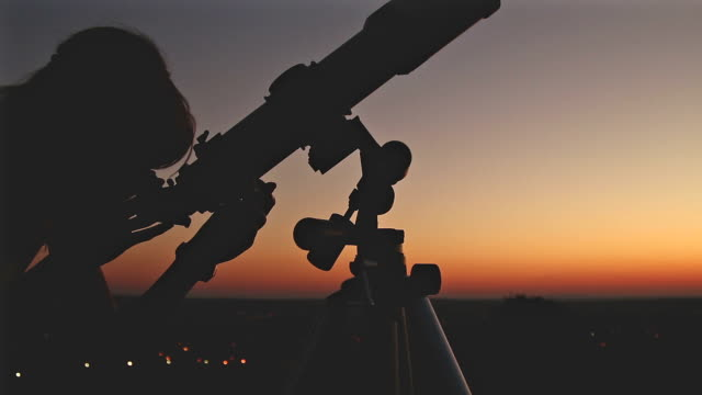 girl looking at the stars with telescope beside her. - astronomia video stock e b–roll