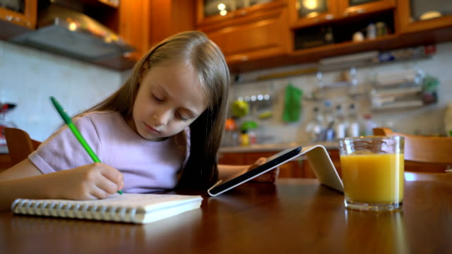 Girl looking at the tablet and handwriting in her journal video