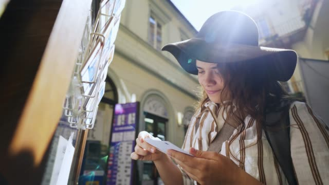 Girl looking greeting cards in souvenir shop on street Young woman looking post cards in souvenir shop at old city centre of Prague. Close-up portrait elegant girl in hat standing on street in backlit while choosing greeting cards on outdoor display souvenir stock videos & royalty-free footage