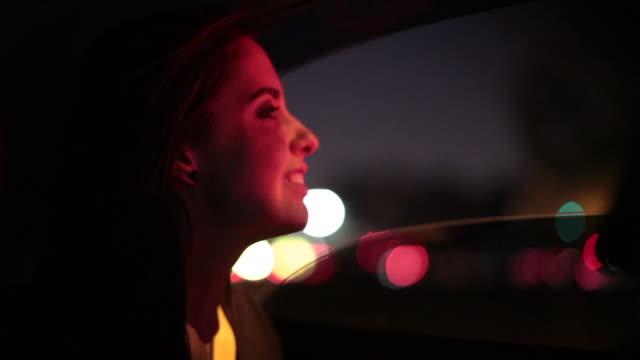 夜に車の窓を探している少女。トラフィックの街の明かりで主演の女性 - 陸の乗り物点の映像素材/bロール