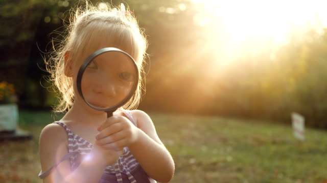 Girl looking through a magnifier at sunset Little girl looking through a magnifying glass magnifying glass stock videos & royalty-free footage