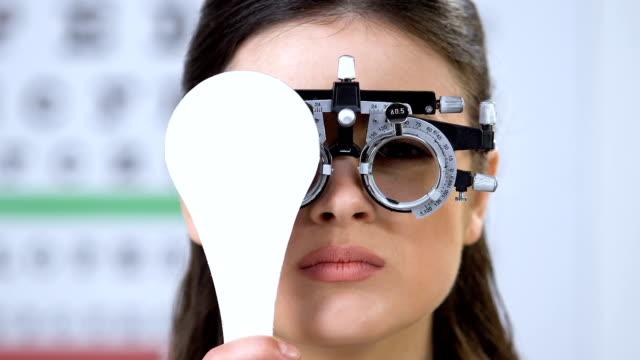 vidéos et rushes de fille regardant avec les yeux partiellement fermés par le phoropter, examen de vision - réfracteur